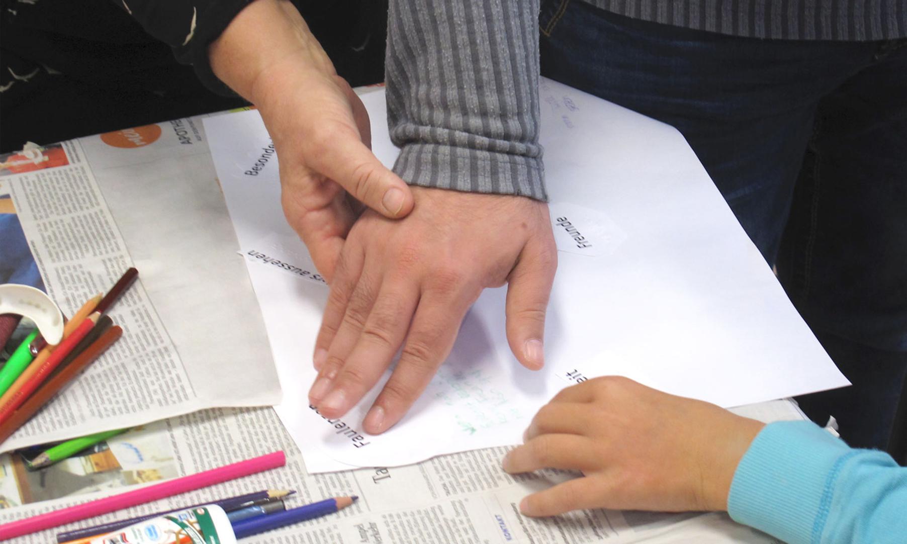 Schulbank mit Workshop-Materialien. Eine Hand führt eine andere Hand zur Brailleschrift.